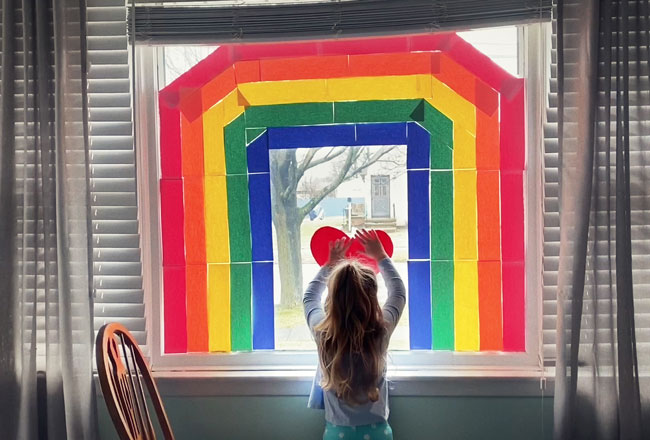 girl at window with rainbow